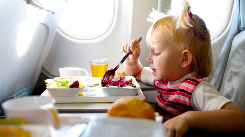 Criança comendo dentro do avião