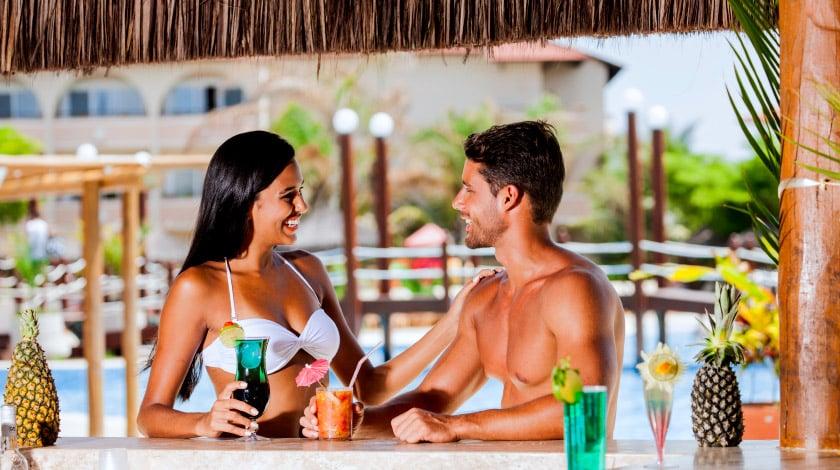 Casal tomando drinks em bar à beira da piscina, no Grand Palladium Imbassaí