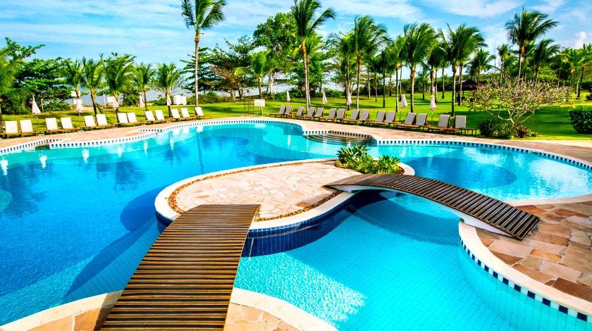 Piscina e coqueiros do resort All-Inclusive Vila Angatu, na Bahia