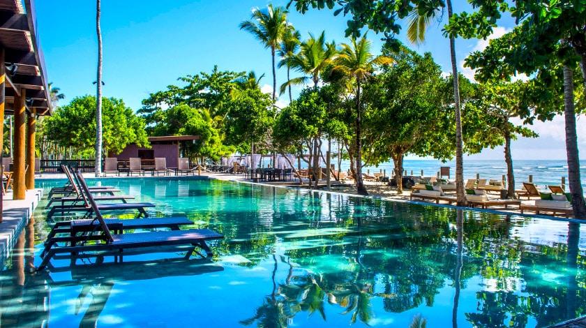 Piscina ao ar livre com espreguiçadeiras e vista para o mar no Kûara Hotel