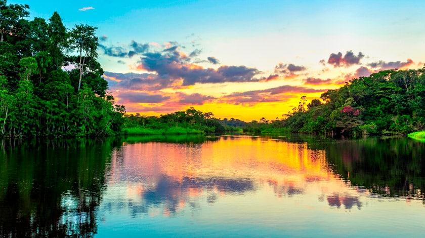 Pôr do sol sobre o rio rodeado pela Floresta Amazônica