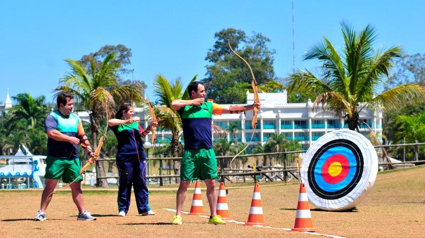 Adultos praticando arco e flecha, atividade oferecida pelo Mavsa Resort