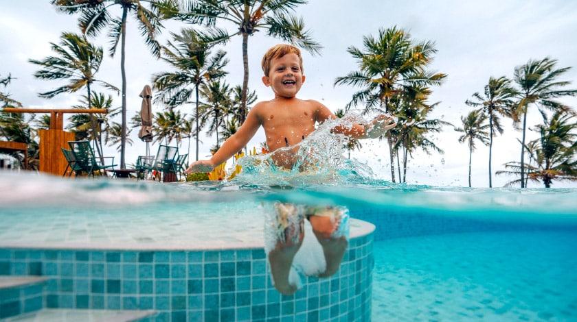 Menino pulando na piscina do Sauípe Premium Brisa All Suítes, para viajar com crianças e descontos Family Trip