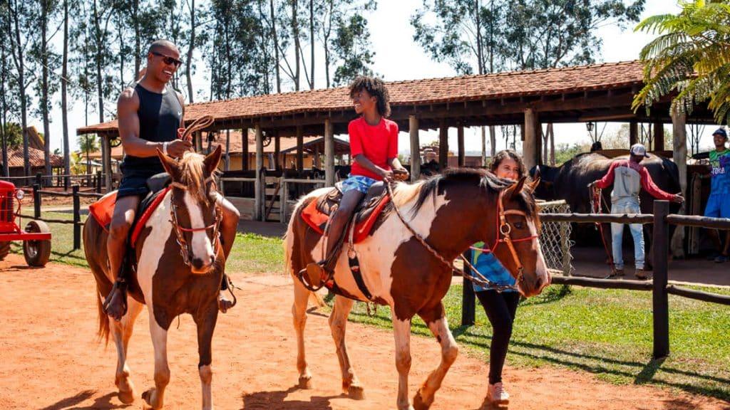 Família andando a cavalo no Barretos Country, um dos resorts na Family Trip