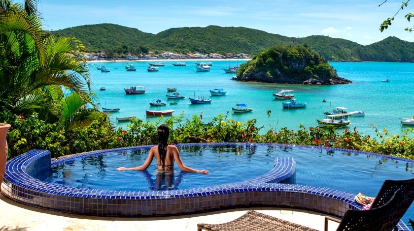 Mulher observando a Praia da Armação na piscina do Vila d'este