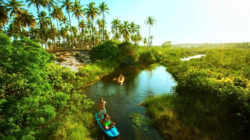 Pessoas praticando stand up paddle no Rio Imbassaí