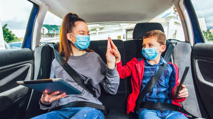 Família viajando de carro durante a pandemia, usando máscaras