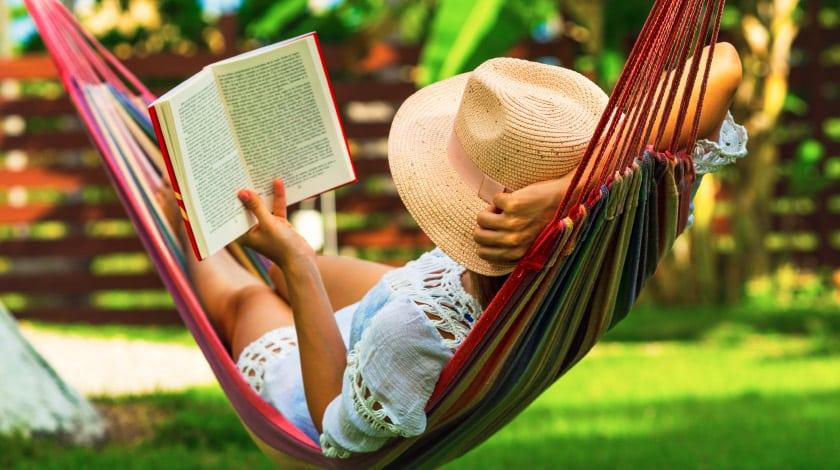Turismo de isolamento: mulher lendo um livro deitada na rede