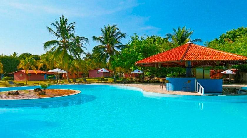 Piscina azul com um quiosque ao lado, no Angá Beach Hotel